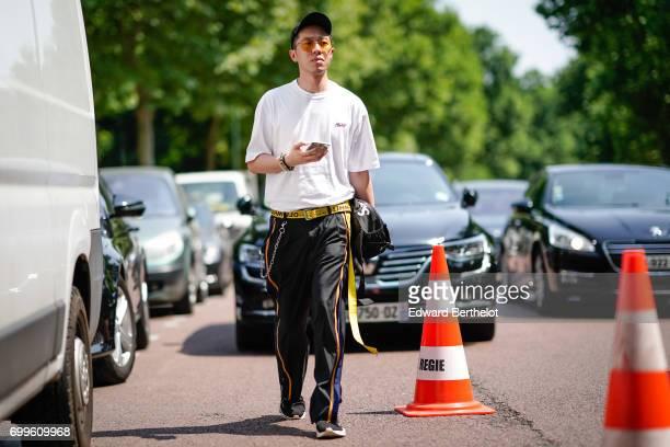 A guest wears sunglasses a cap a white top black pants outside the Balenciaga show during Paris Fashion Week Menswear Spring/Summer 2018 on June 21...