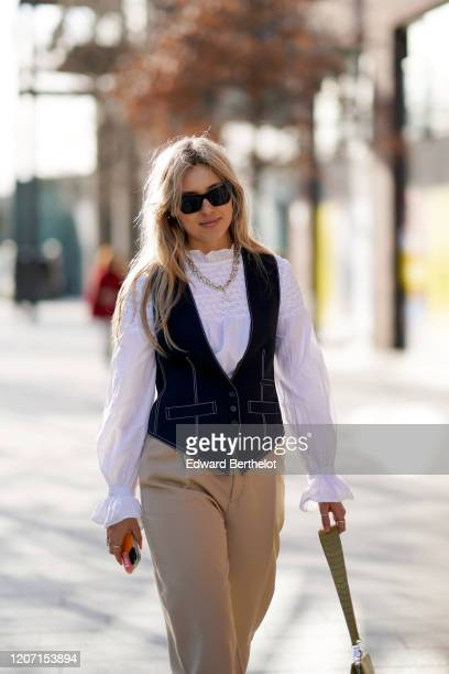 A guest wears sunglasses a chain necklace a white ruffled top a blue sleeveless jacket beige pants a khaki crocodile pattern Ratius and Motus bag...