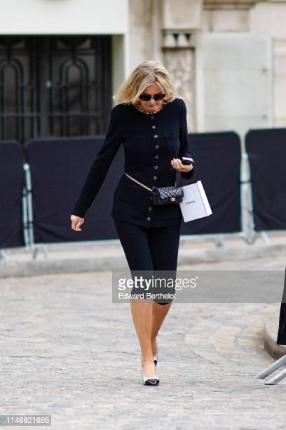 Guest wears sunglasses, a Chanel necklace, a black Chanel jacket, black capris, a black Chanel belt bag, two tons black and white slingback shoes,...