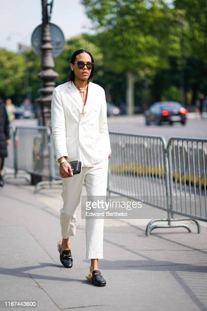 A guest wears sunglasses a Chanel necklace a white doublebreasted jacket matching pants a shiny grey and white minaudiere black leather slippers...