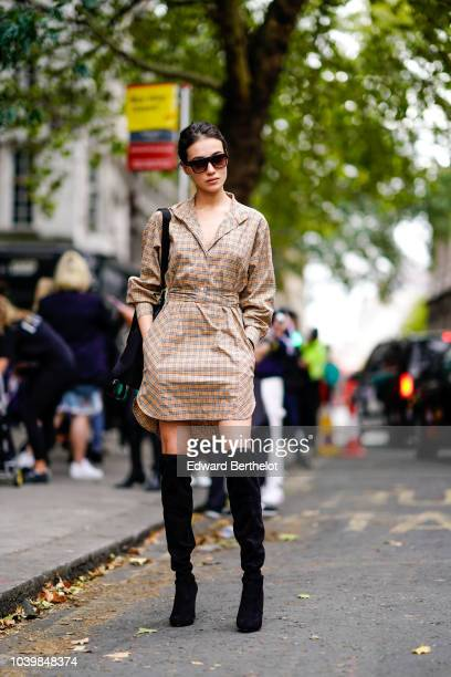A guest wears sunglasses a checked dress black high boots during London Fashion Week September 2018 on September 18 2018 in London England