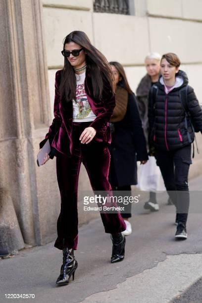 Guest wears sunglasses, a choker, a t-shirt, a purple velvet jacket, purple velvet suit pants, black leather pointy shoes, outside Etro, during Milan...
