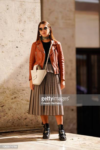 A guest wears sunglasses a choker an orange leather jacket a white bag a pleated skirt black leather boots during Paris Fashion Week Womenswear...