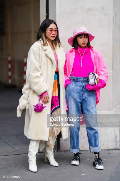 Guest wears sunglasses, a colorful asymmetric pleated dress, a fuchsia clutch, a cream-color fluffy coat, white heeled square-end boots ; A guest...