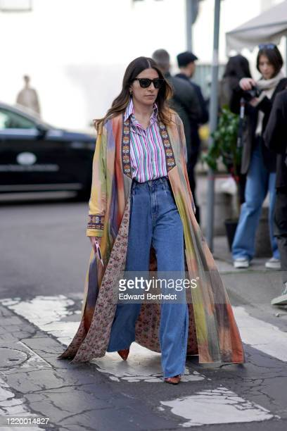 Guest wears sunglasses, a colorful long jacket/cape, a striped shirt, blue jeans, brown leather pointy boots, earrings, outside Etro, during Milan...