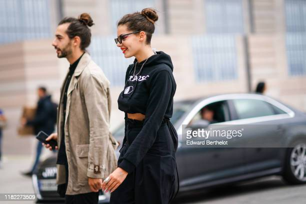 A guest wears sunglasses a cropped hoodie sweater a necklace red lipstick black pants outside Guy Laroche during Paris Fashion Week Womenswear Spring...