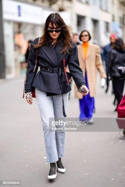 A guest wears sunglasses a darkgrey jacket with an eyelet belt pale blue denim pants white shoes during Paris Fashion Week Womenswear Fall/Winter...
