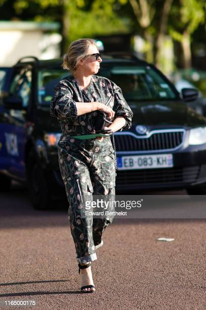A guest wears sunglasses a deep green jumpsuit with pink floral print black strappy heeled sandals outside Miu Miu Club 2020 on June 29 2019 in Paris...