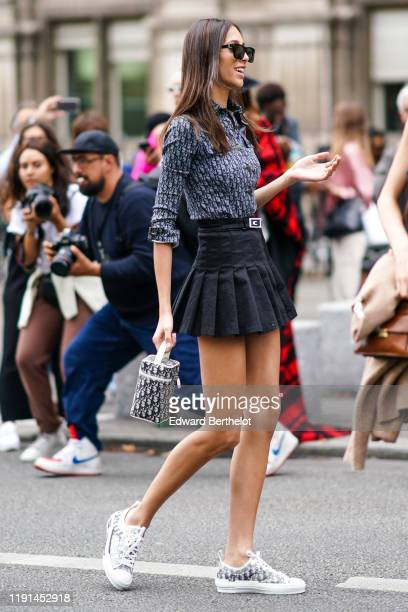 A guest wears sunglasses a Dior monogram logo print shirt a black pleated mini skirt a belt a Dior bag Dior sneakers outside Redemption during Paris...