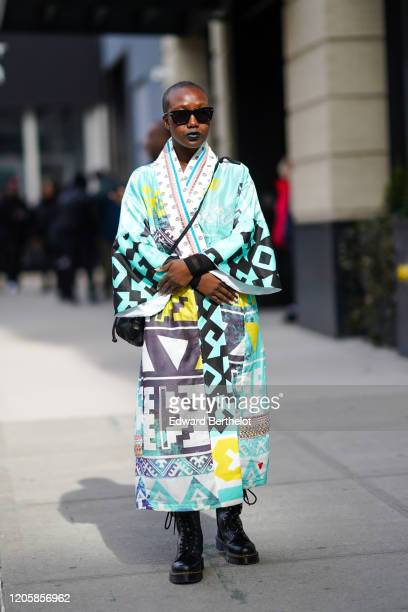 Guest wears sunglasses, a double breasted kimono dress with colored printed geometric patterns, black leather boots, during New York Fashion Week...