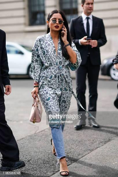 Guest wears sunglasses, a floral print kimono dress, a pink bag, blue ripped jeans, black shoes, outside Elie Saab, during Paris Fashion Week -...