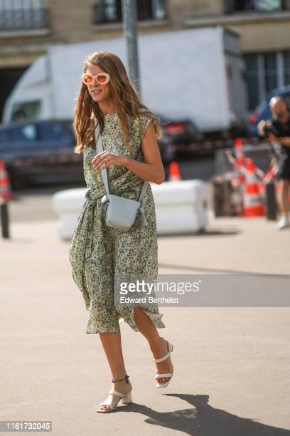 A guest wears sunglasses a floral print light green flowing dress a light grey Acne Studios bag an anklet white strappy mules outside Acne during...