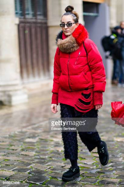 A guest wears sunglasses a fur scarf a red puffer jacket cropped pants shoes outside Thom Browne during Paris Fashion Week Menswear Fall Winter...
