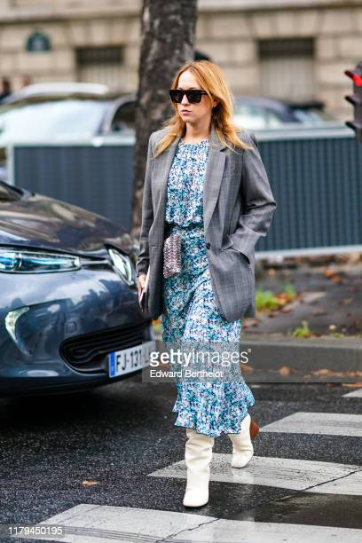 Guest wears sunglasses, a gray blazer jacket, a blue floral print dress, a metallic bag, white boots, outside Miu Miu, during Paris Fashion Week -...