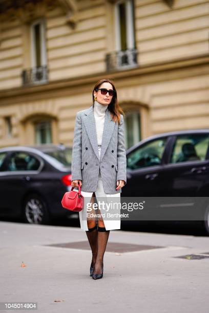 A guest wears sunglasses a gray blazer jacket a white dress a red bag tights black shoes outside Miu Miu during Paris Fashion Week Womenswear...