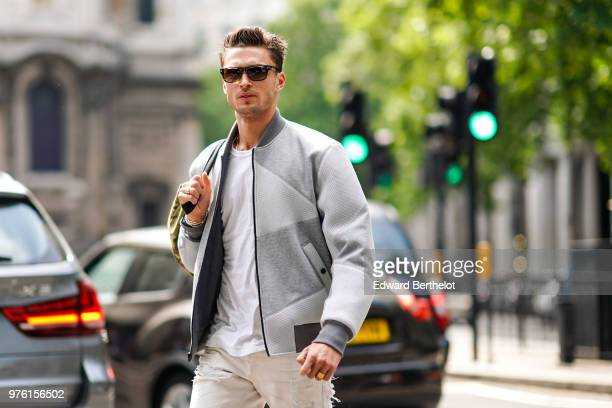 A guest wears sunglasses a gray bomber jacket a bag white pants during London Fashion Week Men's June 2018 on June 10 2018 in London England