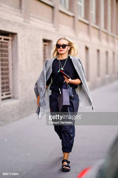 A guest wears sunglasses a gray jacket a black top blue pants sandals outside Wooyoungmi during Paris Fashion Week Menswear SpringSummer 2019 on June...