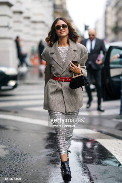 A guest wears sunglasses a gray jacket a red belt a bag a silver shiny glitter sequined dress black leather shoes outside Ralph Russo during Paris...