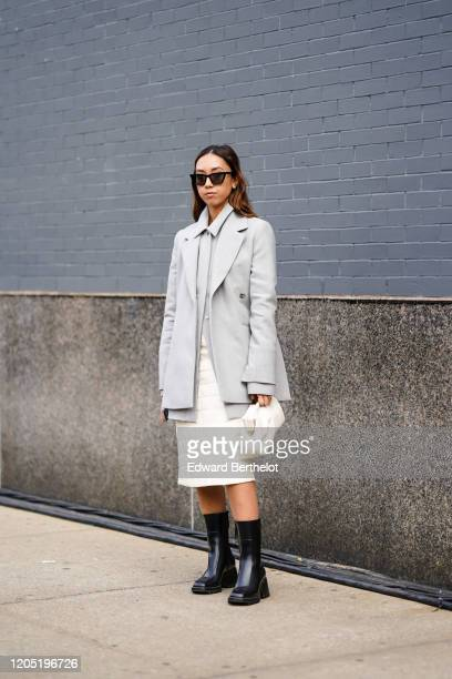 Guest wears sunglasses, a gray jacket, a white quilted skirt, a puff bag, black leather boots, outside Bevza, during New York Fashion Week Fall...