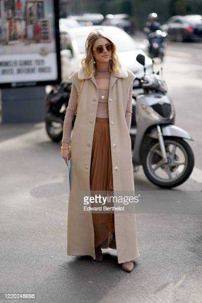 Guest wears sunglasses, a gray long sleeveless coat, a purple top with keyhole, a brown pleated skirt, pointy shoes, outside Sportmax, during Milan...