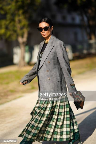 Guest wears sunglasses, a gray oversized blazer jacket, a Gucci bag, a green and white checked pleated skirt, green high heeled leather boots,...