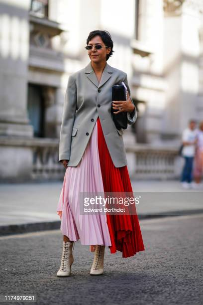 Guest wears sunglasses, a gray oversized jacket, a pink and red pleated skirt, beige shoes, during London Fashion Week September 2019 on September...