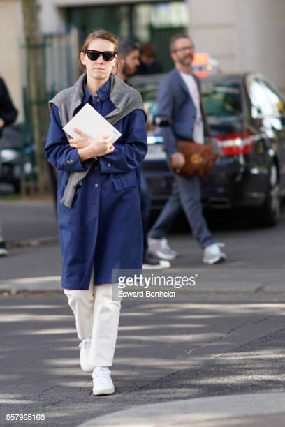 A guest wears sunglasses a gray pull over a blue trench coat white pants white sneakers shoes outside Miu Miu during Paris Fashion Week Womenswear...