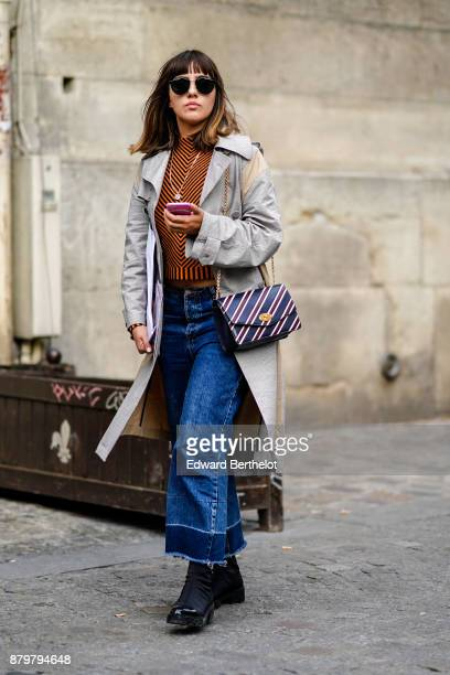 A guest wears sunglasses a gray trench coat blue flare jeans black shoes a striped bag outside Koche during Paris Fashion Week Womenswear...