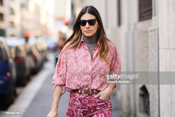 A guest wears sunglasses a gray turtleneck top a pink shirt with printed geometric patterns pink pants a brown leather belt outside Etro during Milan...