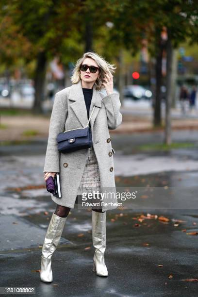 Guest wears sunglasses, a gray wool long coat, a Chanel bag, silver long pointy shiny boots, tights, a white tweed skirt, a black top, earrings,...