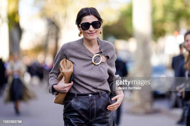 A guest wears sunglasses a gray wool pullover with a metallic ring black leather pants a brown leather bag outside Haider Ackermann during Paris...
