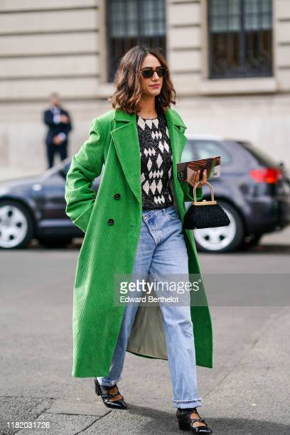 Guest wears sunglasses, a green corduroy long coat, a black and white geometric pattern print pullover, blue denim jeans pants, black leather pointy...