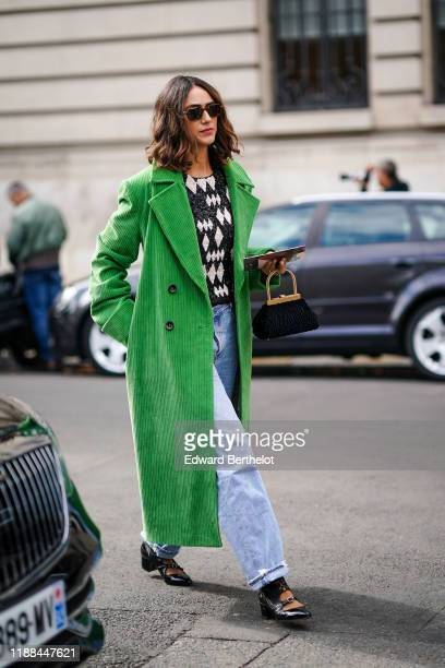 Guest wears sunglasses, a green corduroy long coat, blue denim jeans, black pointy shoes, a black and white top with printed diamond shapes, a bag...