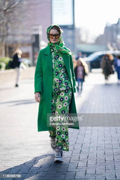 Guest wears sunglasses, a green floral print scarf, a green coat, a green floral print shirt, green floral print pants, colorful sneakers, a colorful...