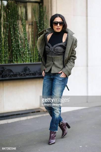A guest wears sunglasses a green jacket an off shoulder turtleneck black top blue denim jeans pants and purple leather boots outside the Balmain show...