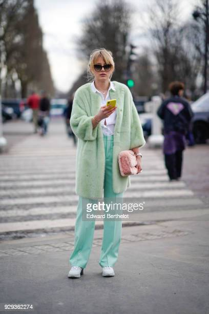 A guest wears sunglasses a green jacket green pants white sneakers shoes pink bag outside Chanel during Paris Fashion Week Womenswear Fall/Winter...