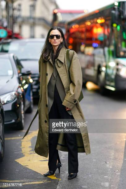 Guest wears sunglasses, a green khaki long trench coat, black pants, pointy shoes, outside Redemption, during Paris Fashion Week - Womenswear...