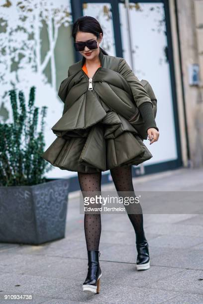 A guest wears sunglasses a green khaki puffer dress tights black leather shoes outside Viktor Rolf during Paris Fashion Week Haute Couture...