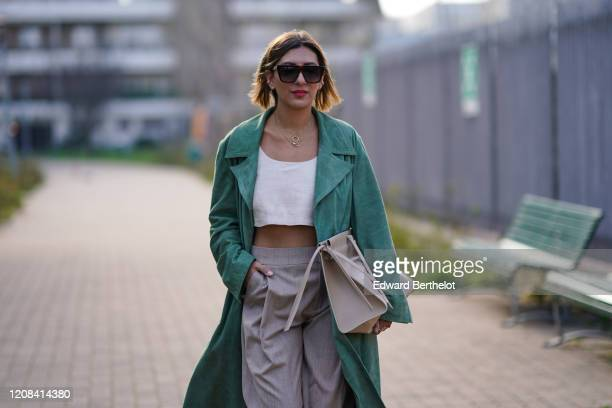 A guest wears sunglasses a green long coat a white cropped top gray pants white pointy shoes outside BOSS during Milan Fashion Week Fall/Winter...