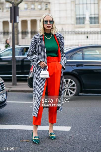 Guest wears sunglasses, a green pullover, a necklace, a black and white checked pattern printed trench coat, a white Jacquemus mini bag, red crop...