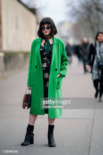 Guest wears sunglasses, a green scarf, a green coat, a black floral print dress, black ankle boots with separated end, outside Valentino, during...