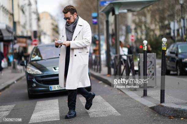Guest wears sunglasses, a grey and black scarf, a white trench coat, black pants, black square toe and quilted shoes, outside Paul Smith, during...