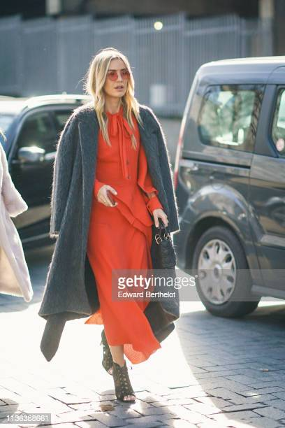 A guest wears sunglasses a grey coat a red flowing dress with a bow collar a black Lady Dior handbag black peeptoed lace up heeled pumps during...