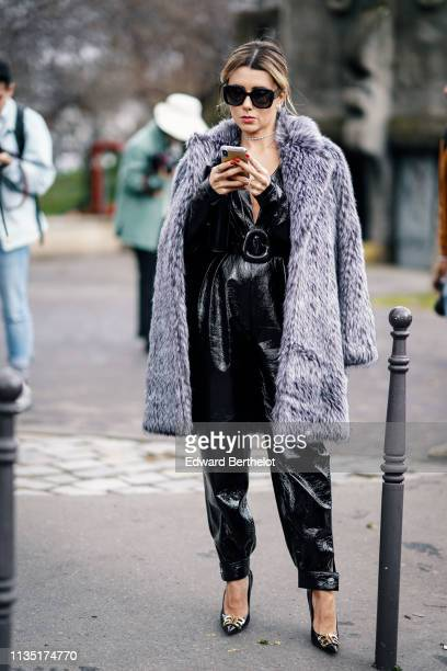 Guest wears sunglasses, a grey fluffy faux fur coat, a strass necklace, a shiny black low-cut jumpsuit, black Balenciaga pointy high-heeled pumps,...