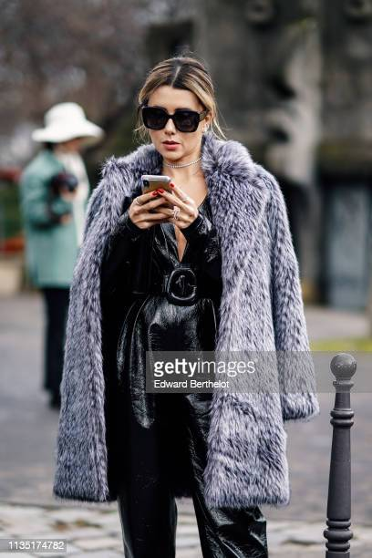 A guest wears sunglasses a grey fluffy faux fur coat a strass necklace a shiny black lowcut jumpsuit black Balenciaga pointy highheeled pumps outside...