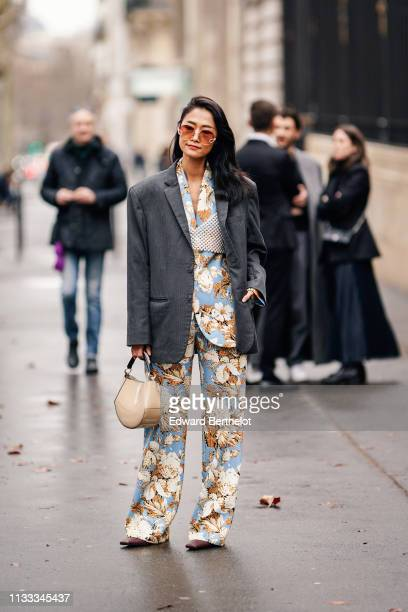 A guest wears sunglasses a grey jacket a shiny beige handbag a beaded bra over a camel and blue floral print pantsuit with oversize pants outside...