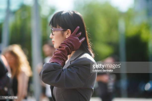 A guest wears sunglasses a grey jumpsuit brown gloves outside Acne during Paris Fashion Week Haute Couture Fall/Winter 2019/2020 on June 30 2019 in...