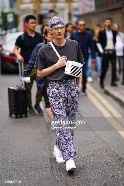A guest wears sunglasses a grey python pattern head scarf a grey tshirt a white bag with black stripes grey python pattern pants with a sliding belt...