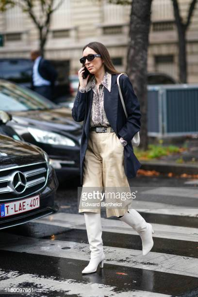 A guest wears sunglasses a grey python pattern shirt a grey python pattern belt a beige leather divided skirt a navy blue Prince of Wales check...