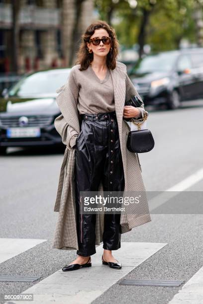 A guest wears sunglasses a grey Vneck top a black and white houndstooth trenchcoat black shiny baggy pants with a large zip a black eyelet belt black...